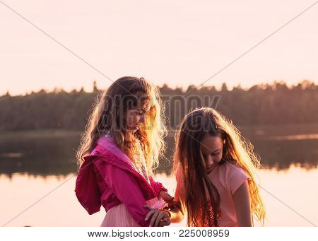 Two beautiful little girls smiling and playing at the seaside during sunset