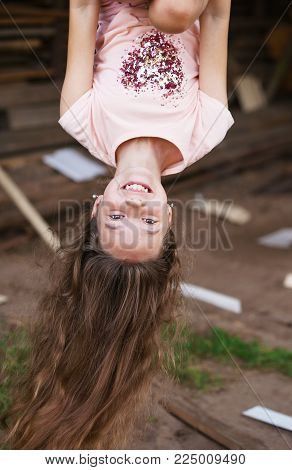 Beautiful little girl with long hair hanging upside down and smiling