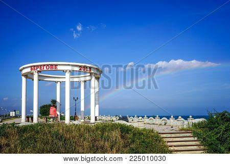 Feodosia, Crimea - June 16, 2016: The white rotunda near the beach in the area of Feodosia on the background of blue sky and rainbow over the sea.