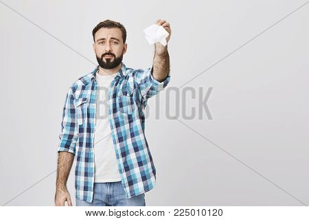 Indoor shot of gloomy sad bearded adult man holding tissue in hand and waving it like saying goodbye, standing over gray background. Father send off daughter to summer camp for the first time. Copy space