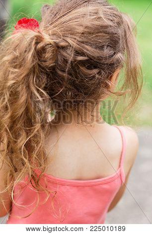 Child girl outside with long curly hair, back view