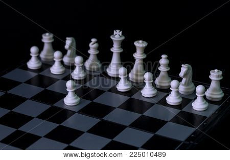 White chess figures on board. White chess set in order for game start. White pawn E2-E4 move on checkered board. Chess figurine order. Checkmate game banner template. Intellectual sport. Tactic game