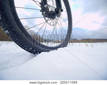 Winter snow riding on mountine bike. Extreme weather, slippery road in field, close low ankle wide view to front wheel.