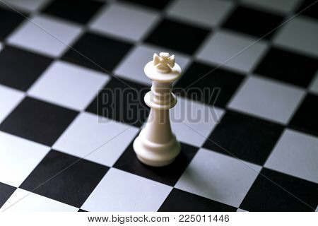 Chess figure white king on chess board. Chess game. Checkered board. White king alone on chessboard. Mate situation in chess rules. Business advantage or strong leadership concept. White king closeup