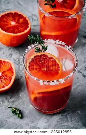 Blood Orange Sparkling Vodka cocktail on dark gray concrete background