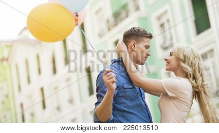Blonde girl embracing beloved young man, couple dating, holding balloons, stock video