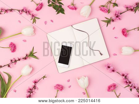 businesswoman, connection, industrial life concept. wonderful flatlay composed of the mobile phone and clean daily planner surrounded with different flowers such as tulips, roses, oriental cherry