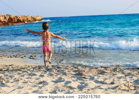 Happy  Cute Little Girl running  on the coast of warm Sea at Summer Sunset