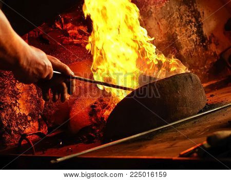 Detail of blacksmith s forge with strong flames. Hands setting up fire in forge.