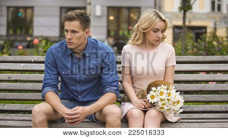 Unhappy couple sitting after fight, girl with flowers, problem in relationship, stock video