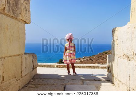 Cute  baby girl in beautiful dress looking at the sea on a sunny day. Little girl  standing back on the shore of the sea. Sun, warm day, childhood