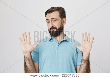 Portrait of handsome european bearded man, raising hands in surrender gesture, smiling and looking uncertain, standing over gray background. Fine, you won, I am out of this.
