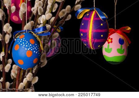 Three colored easter eggs on willow bouquet with pussy willows. Religious decoration. Paschal eggs on branches with furry catkins in a vase. Salix. Front view, horizontal, on black background. Photo.