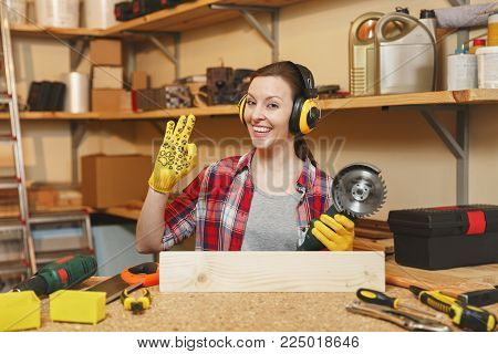 Young woman in plaid shirt gray T-shirt noise insulated headphones yellow gloves working in carpentry workshop at wooden table place with different tools showing OK gesture, sawing wood with saw