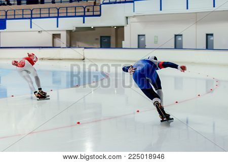 back two athletes skater on competition in speed skating
