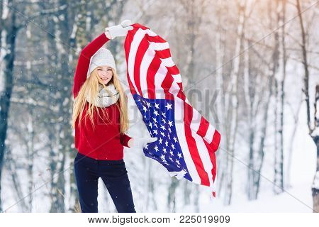 Winter young woman portrait. Beauty Joyful Model Girl laughing and having fun in winter park. Beautiful young woman laughing outdoors with USA flag. Enjoying nature, wintertime.