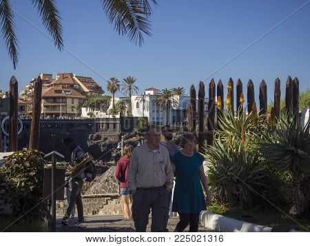 Spain, Canary islands, Tenerife, Puerto de la cruz, December 23, 2017, senior tourist couple walking on main promenade wtih tropical flowers street seller, city walls and blue sky background