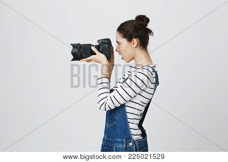 Profile of hipster girl holding photo camera in hands, taking photos. Brunette photographer with two hairbuns in denim overall concentrated on her work, posing against gray background