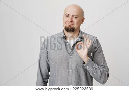 Portrait of attractive smiling bald man with beard showing okay sign and standing with not bad expression over gray background. Son introduced his girlfriend to parents and dad approves. Emotions concept.