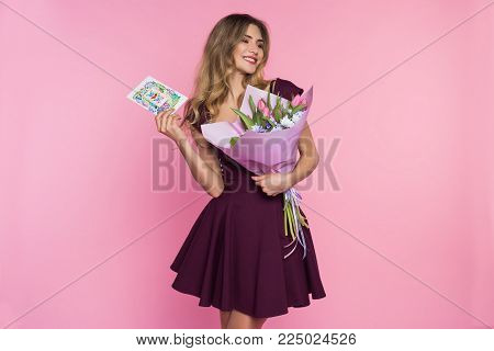 Charming, pretty girl is holding a big tulip bouquet in hands. Lady is showing a card. Pink background. Happy woman's day