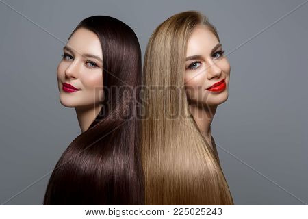 two beautiful young women with healthy shiny straight hair. blonde and brunette with red lips. studio beauty shot. copy space.