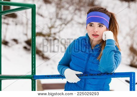 Outdoor sport exercises, sporty outfit ideas. Woman wearing warm sportswear relaxing after exercising outside during winter.