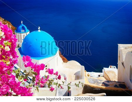 traditional blue dome of church and blue sea water, Oia, Santorini with flowers