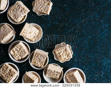 Homemade square bars of Marshmallow and crispy rice and ingredients on dark blue background. American dessert with marshmallow and crispy rice. Top view. Copy space