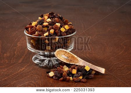 raisins currants and sultanas with mixed candied peel in a glass bowl with wood spoon