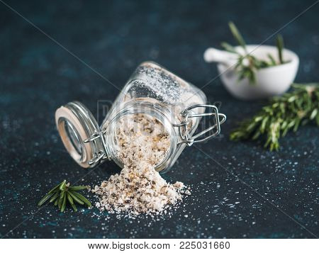 Sea salt scented herb rosemary and lemon zest. Sea salt with aromatic herb spilled out of glass jar on dark blue background. Scented salt and ingerdients. Copy space