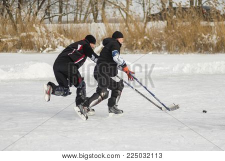 Dnipro, Ukraine - January 27, 2018: Two mature amateur men playing hockey on a frozen river Dnepr in Ukraine