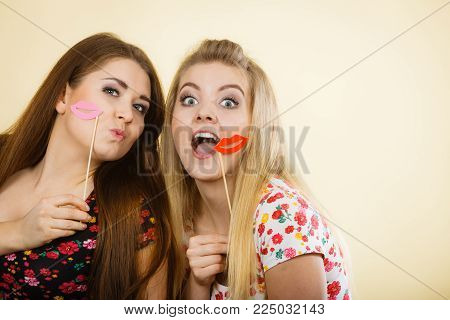 Two happy women holding fake lips on stick having fun wearing tshirts with flower pattern. Photo and carnival funny accessories concept.