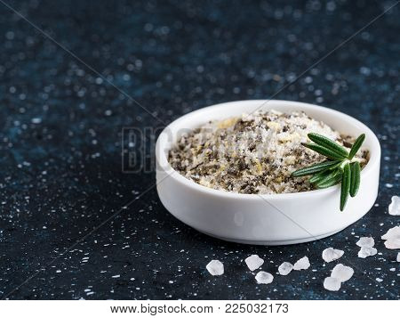 Sea salt scented herb rosemary and lemon zest. Sea salt with aromatic herbin small bowl on dark blue background. Scented salt and ingerdients. Copy space