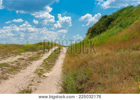 Sandy country road leading on a hill at summer season in Ukraine
