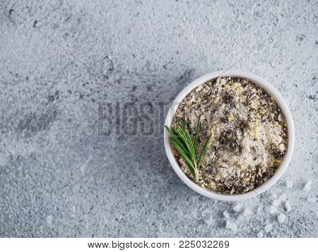 Sea salt scented herb rosemary and lemon zest. Sea salt with aromatic herbin small bowl on gray cement background. Scented salt and ingerdients. Copy space. Top view or flat lay