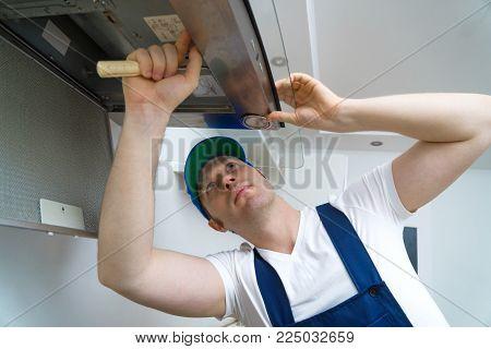 Handsome foreman fixing exhaust hood in the kitchen.