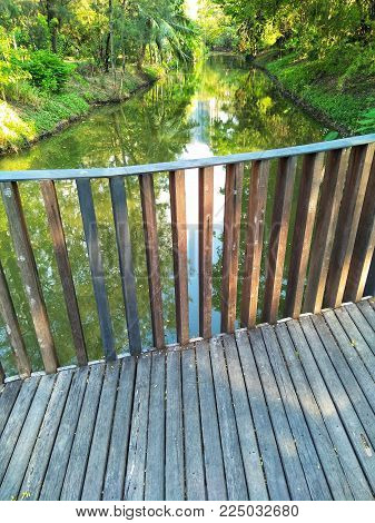 Old wooden bridge across the small canal with wooden handrails and water view, Green nature with warm light and park in the city