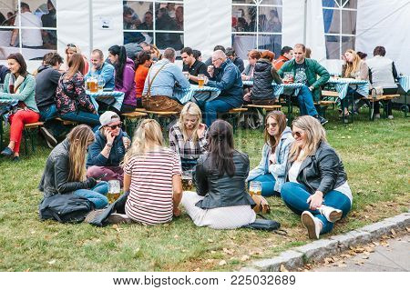 Prague, September 23, 2017: Celebrating the traditional German beer festival called Oktoberfest in the Czech Republic.Young girl friends sitting on the grass talking and drinking fresh beer