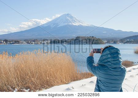 Asian woman traveler taking photograph beautiful landscape view of fuji mountain covered with white snow in winter seasonal at Yamanaka Lake, Japan.