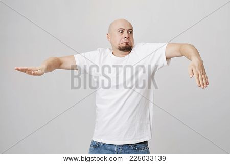 Indoor portrait of funny bald bearded european guy who is doing wave dance while standing over gray background in white t-shirt and jeans. It is never too late to start learning how to breakdance,