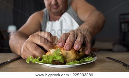 Bad mannered man tearing greasy fried chicken with fingers, fatty food addiction, stock footage
