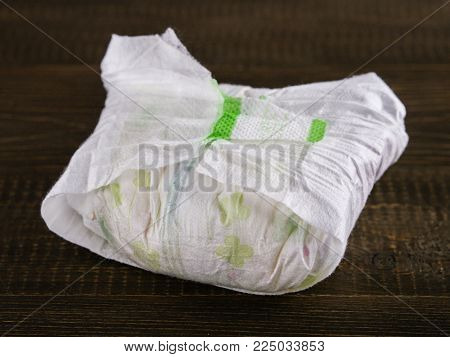 dirty diaper on dark wooden background, selective focus