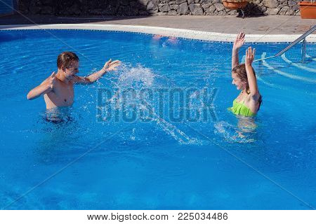teen age boy and girl having fun in oudoor swimming pool. brother and sister on Tenerife island resort. copy space.