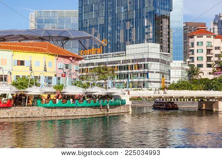 CLARKE QUAY, SINGAPORE - AUGUST 17, 2009: A traditional bumboat on the Singapore River passes under a bridge at Clarke Quay with a hotel and skyscrapers in the background.