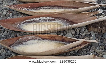 Production of sea salt in the Bali, Indonesia. Salt crystallizes out of the ground in salt farm, filled with natural salt from the sea.