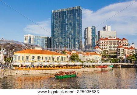 CLARKE QUAY, SINGAPORE - AUGUST 17, 2009: A traditional bumboat on the Singapore River passes Clarke Quay with skyscrapers in the background.