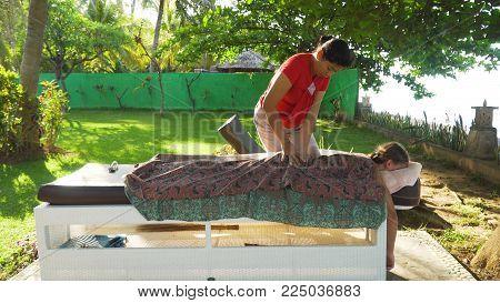 Asian woman massage therapist doing massage to girl. Summer vacation on luxury spa resort, massage procedure on the beach. Young woman enjoying a massage outside. Bali, Indonesia.