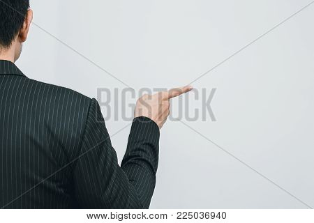 Asian business man pointing his finger to touch or order command back view on white space