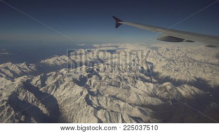 Mountain range with snow from the airplane window. Airplane wing. Aerial view on snowy mountains through window of an aircraft. Mountain from the airplane window. Travel concept.