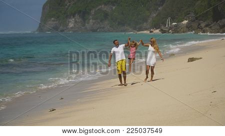 Happy beautiful family with child walking together on tropical beach during summer vacation. Bali. Family of three having fun on tropical beach. Travel concept. Family relationships